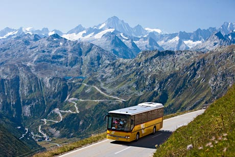 Postauto auf dem Furkapass im Kanton Wallis. Blick auf die Grimselpassstrasse, überragt vom Finsteraarhorn (4274 m). Copyright by: Switzerland Tourism By-Line: swiss-image.ch/Christof Sonderegger