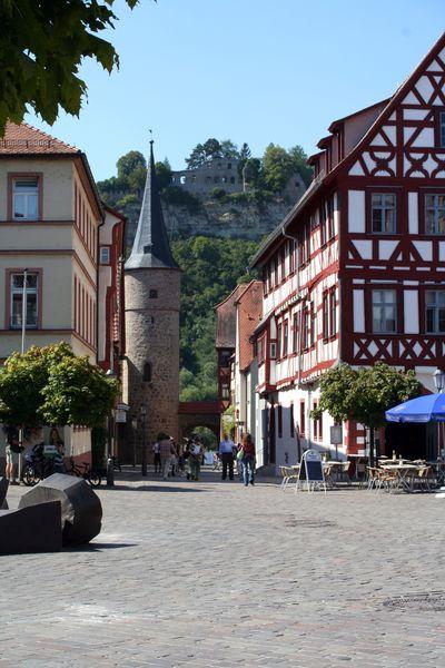 Blick auf ein Stadttor von Karlstadt, im Hintergrund ist die Ruine der Karlsburg zu sehen. Foto: djd/Stadt Karlstadt