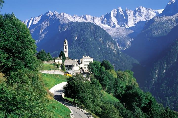 Postauto im Kanton Graubünden: das Dorf Soglio im Bergell, im Hintergrund die Sciora-Bergkette. © Die Post/Schweiz Tourismus (ST/swiss-image.ch)